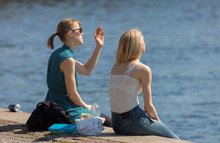 fair skinned: STOCKHOLM SWEDEN 4 May 2016. Lunch at the quayside. Two young women sit in the sun in Stockholm. Editorial
