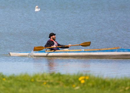 paddles: YTTERJARNA SWEDEN 12 May 2016 Man in hat paddles kayak.