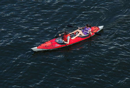 joyride: STOCKHOLM SWEDEN July 15, 2015. Two people paddling in a kayak. Photographed from one of the bridges of Stockholm