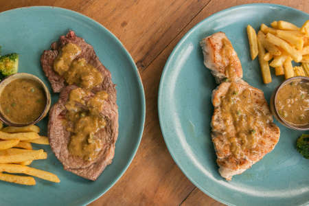 western food: 2 plates of pork steak, french fries, and vegetable on a wooden table - Western food