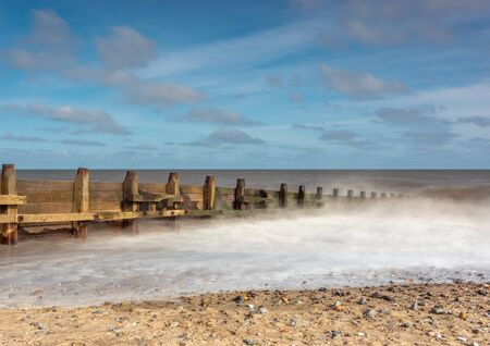 Groin sea defences with craching waves Stock Photo