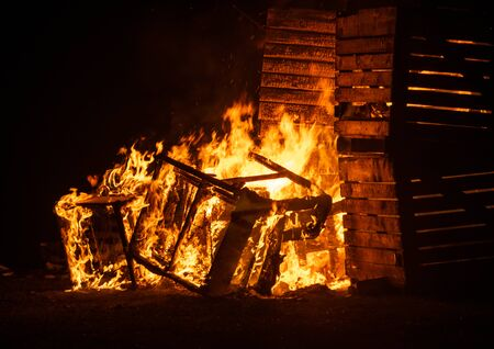 A fire of wooden crates set alight during darkness with bright orange flames and a dark background Stock Photo