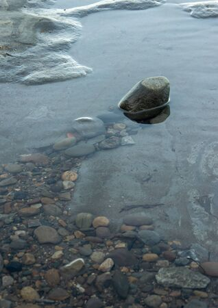 A single rock above the surface in a rock pool with submerged pebbles leading to it.