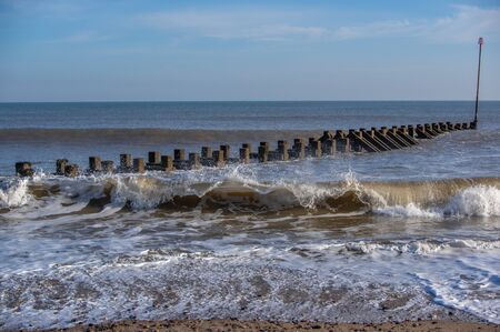 A weathered wooden groin at Hornsea beach with small waves and a blue sky