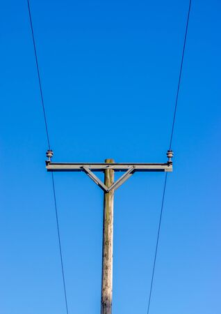 Two power lines on insulators on a wooden telegraph pole with a blue background