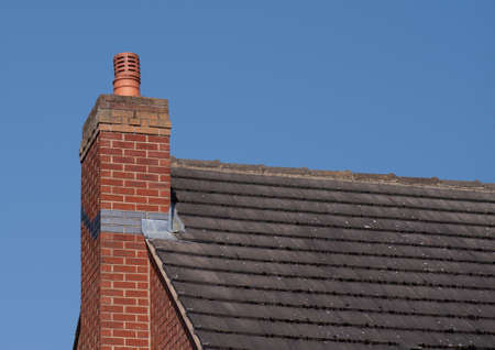 Chimney pot on red brick chimney stack and tiled roof
