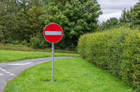A red and white no entry sign on a metal post on a country road with a green hedge background. Stock Photo