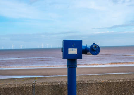 Coin operated telescope on the sea front at Withernsea with view of off shore wind farm in the distance.