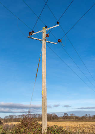 Wooden telegraph poles with wires against a clear blue sky