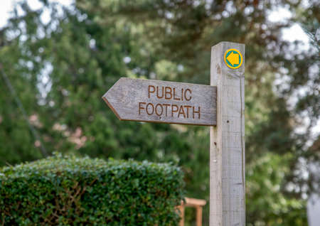 A wooden arrow sign post with Public Footpath on it and trees in background.