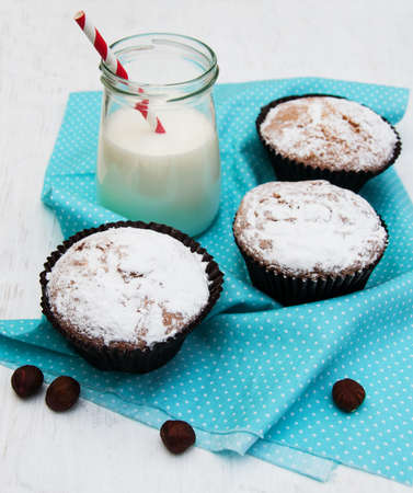 cupcakes and milk on a old white wooden background photo