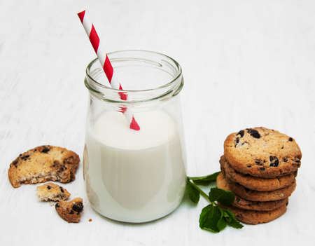 Glass of milk and cookies on a old white wooden background photo