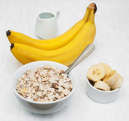 Banana and muesli on a old white wooden background