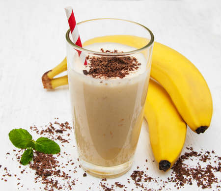 Banana smoothie with chocolate on a old white wooden background