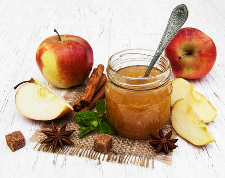 Apple jam and fresh apple on a wooden background
