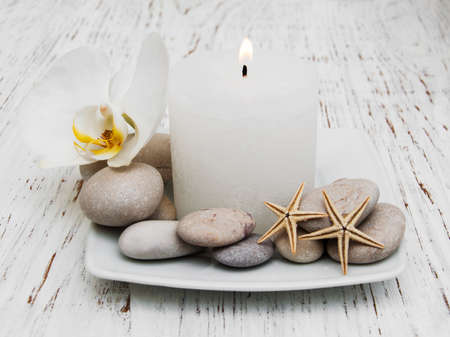 zen candles: Spa set - candle, orchid flower and pebble on a wooden background