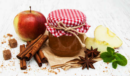Apple jam and fresh apple on a wooden background photo