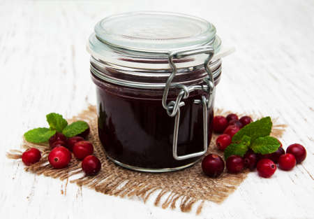 jar of cranberry jam with fresh fruits on a old wooden background photo