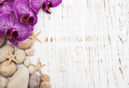 Orchids and massage stones on a wooden background photo