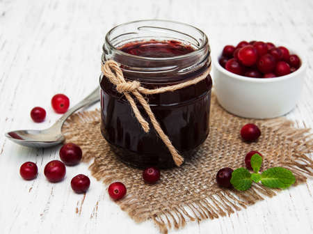 cranberry jam with fresh fruits on a old wooden background photo