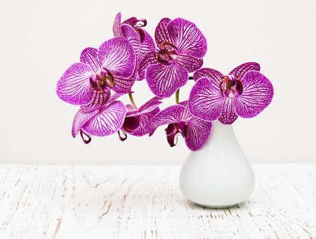 arreglo floral: flores de la orquídea púrpura en florero en una mesa de madera Foto de archivo