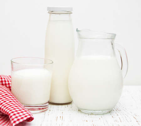 pasteurized: Jar, bottle and glass with fresh milk on a wooden background Stock Photo