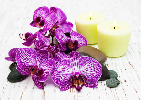 Candles, orchids and massage stones on a wooden background photo