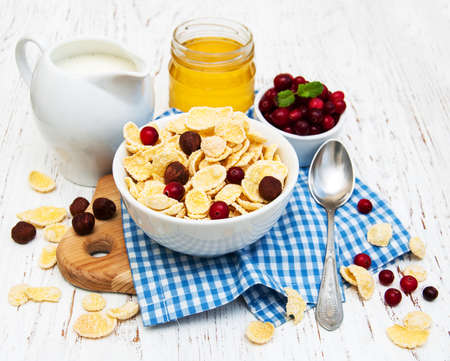 breakfast food: cornflakes with milk, cranberries and nuts on a wooden table