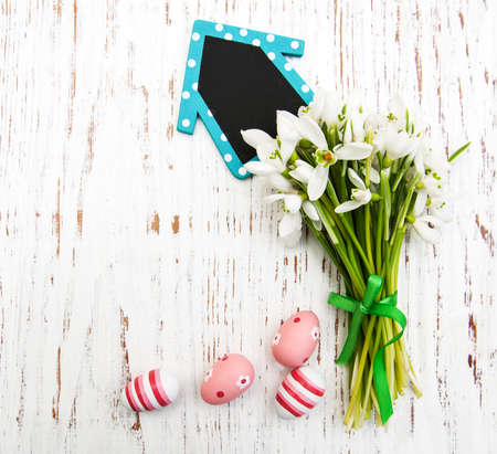 Eggs and spring snowdrops with board on a wooden background photo