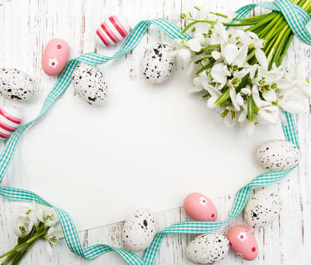season greetings: Easter background with snowdrops, eggs and ribbon Stock Photo