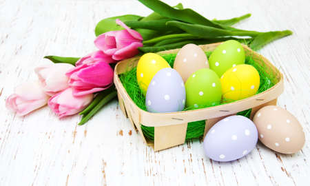 Basket with easter eggs and pink tulips on a old wooden background photo