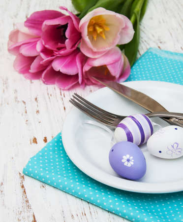 Easter table setting with easter eggs and pink tulips photo