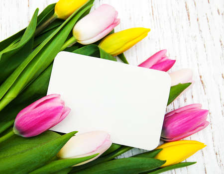 Pink and yellow tulips with a card on a white wooden background photo