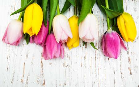 flor morada: frontera de tulipanes de color rosa y amarillo sobre un fondo de madera