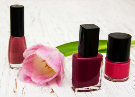 color nail polish bottles and tulip on a wooden background photo