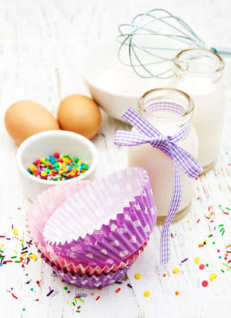 needed: ingredients needed for baking cupcakes on a old wooden background