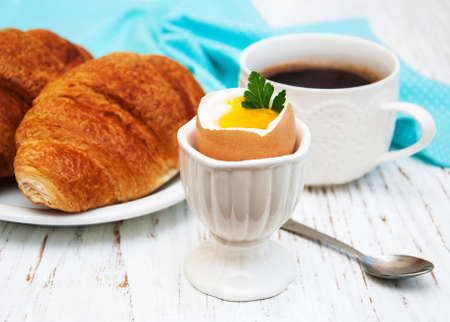 eggcup: croissant, boiled egg and coffee on a old wooden table