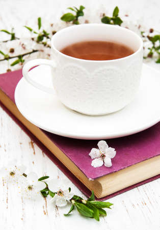 herbal knowledge: Cup of tea and cherry blossom with old book on a wooden background