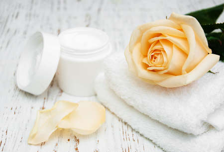 moisturiser: Rose with moisturiser cream and towels on a wooden background Stock Photo