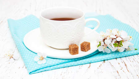 Cup of tea and spring apricot blossom on a wooden background photo