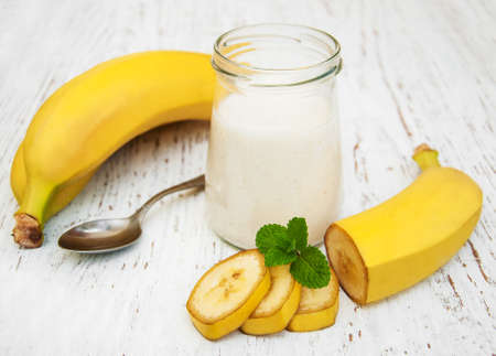 Banana yogurt and fresh bananas on a wooden background