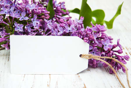 Lilac flowers with empty tag on a old wooden background