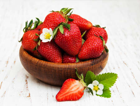 frutilla: Bowl with strawberries on a old wooden background