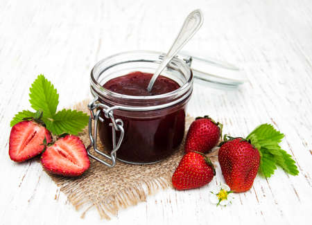 canned food: Strawberry jam and fresh strawberries on a wooden background