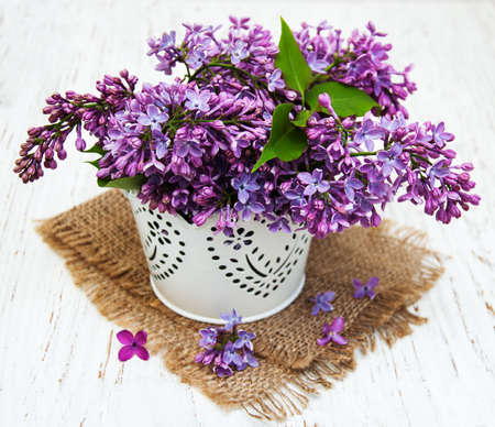 vases: Lilac flowers on a old wooden background
