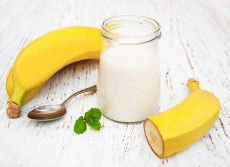 licuado de platano: Yogur de plátano y banano fresco en un fondo de madera Foto de archivo