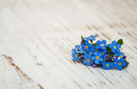 blue romance: Forget-me-nots flowers with ribbon on a wooden background