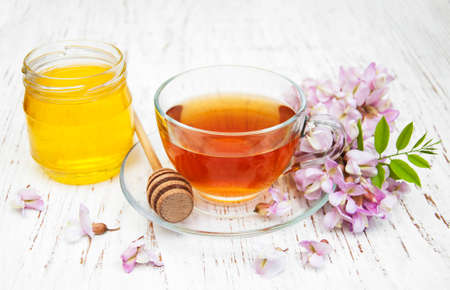 Cup of tea, honey and acacia flowers on a wooden background photo