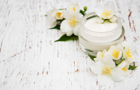 face and body cream moisturizers with jasmine flowers on white wooden background Imagens