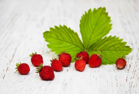 Wild strawberries on a old white wooden background photo